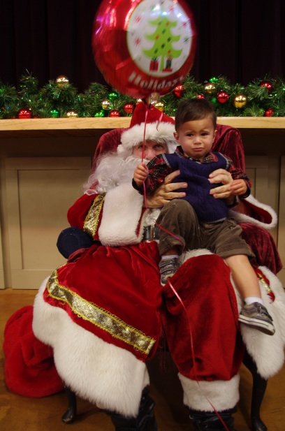Even a big red holiday balloon can't stop Thomas' tears as he sits on Santa's lap.