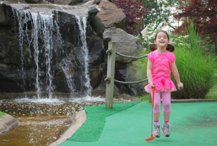 Little girl jumping mini golf