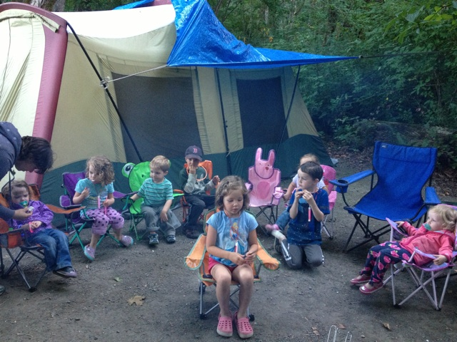 Group of kids around campfire with tent