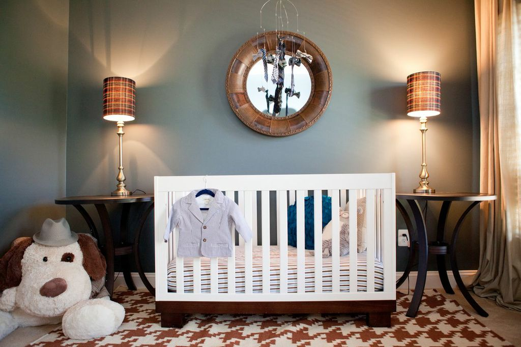 "This room was inspired by Menswear and I call it ""Well Suited"". A nursery doesn't have to be the ""Nursery in the Bag"" purchase.Think outside of the box. There are no rules when it comes to design. Since I am budget conscious and like to change my home often, I like to buy items that can be used in any room in my home. Therefore, I stay away from kiddie themed items..but the nursery still feels warm and ready for a child. In this case, I like different textures/patterns together on a well dressed man so I decided to translate it to a room. Source: The wall paint color is Behr: Amphibian, Trim/Ceiling: Sherwin Williams: Amber White. The plaid lamps, studded mirror, plaid pillow cover and storage containers came from HomeGoods. The Amber colored Houndstooth Rug is from Garnet Hill(clearance). The blinds and side tables which are outdoor tables are from Lowe's (clearance). The glass lantern, striped sheets and tweed magazine holder are from Target (clearance). The Mayfair Steamer Trunk is from Restoration Hardware outlet (deeply discounted). The Luca glider is from Monte (in Stone with charcoal piping) and is recycled from my previous nursery which I ordered from Pink and Brown Boutique. The stuffed puppy is from Sam's Club. The boy's clip on ties, bow ties, hats, and stuffed animal clothing came mostly from thrift stores. The crib is the two toned Babyletto Modo crib which can be purchased online at a number of stores (also recycled from the previous nursery). Curtains are from Ikea."