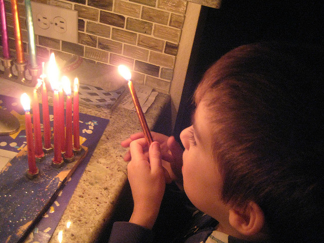 kid-lighting-menorah