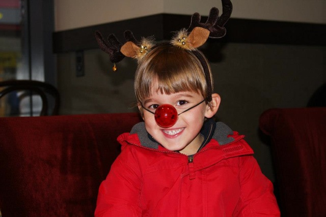 Little kid with rudolph antlers and nose