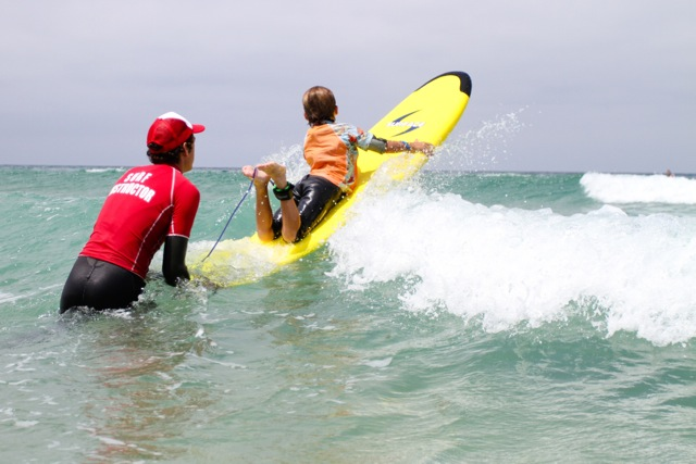 SurfDiva - instructor with kid in waves