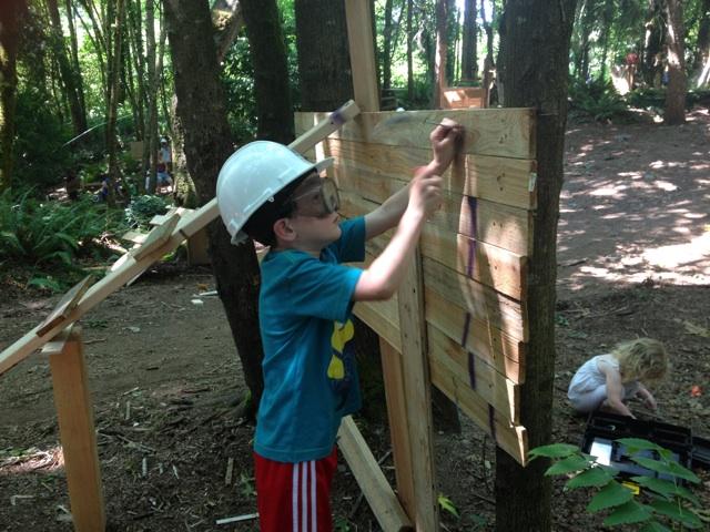 Boy hammering board Adventure Playground
