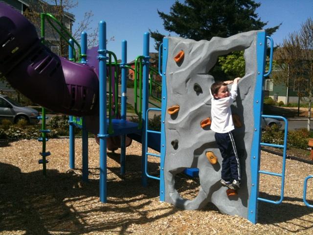 Boy climbing wall on playground