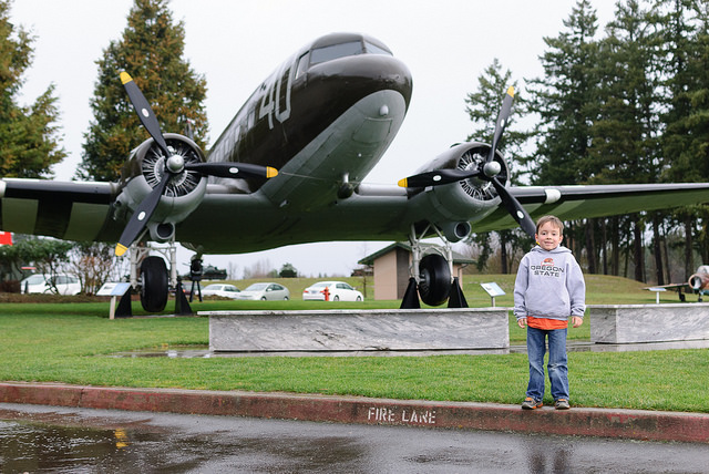 boy standing in front of airplane
