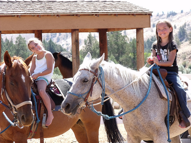 Two girls smiling on horseback