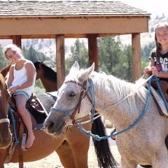 Two girls smiling on horseback