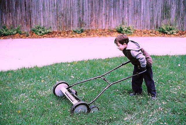 kid mowing a lawn