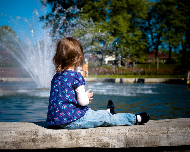 Child sitting near fountain