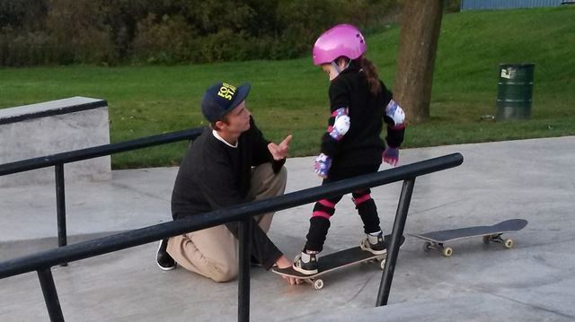 A teenager offers skateboard tips to six-year-old Peyton at a skate park in Cambridge, Ont. in a recent handout photo. A southern Ontario mom is hoping to thank an anonymous teenage boy for helping break down gender barriers for her six-year-old daughter. THE CANADIAN PRESS/HO-Jeanean Thomas