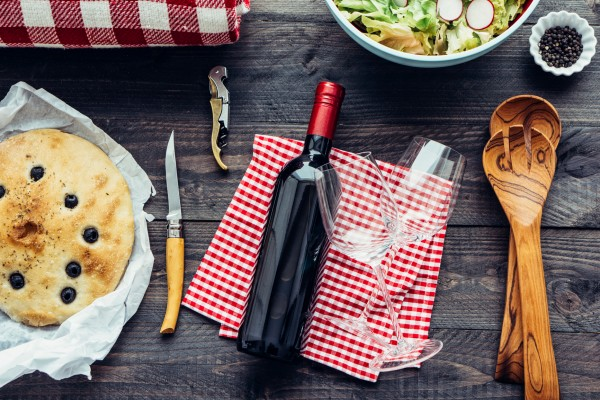 Food: Picnic ingredients on dark wood with red wine bottle, brea
