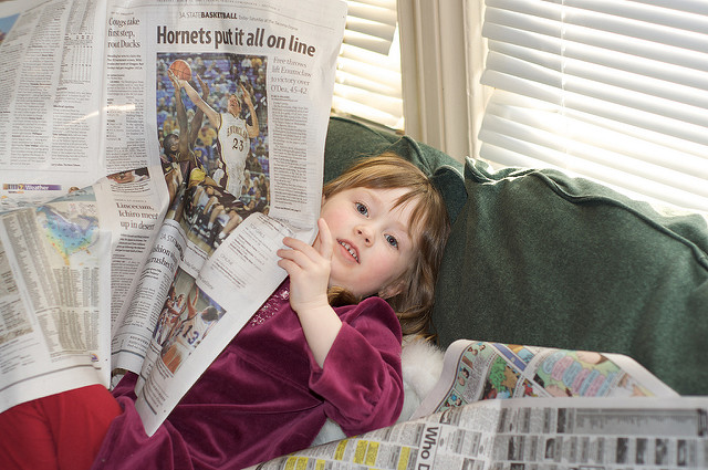kid with newspaper reading