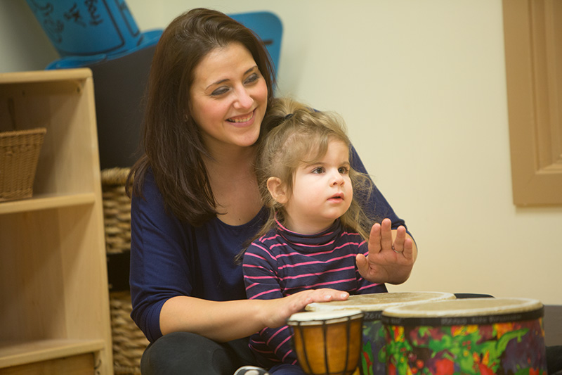 child drumming with adult