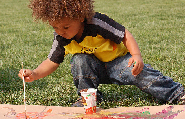 Kid painting on grass