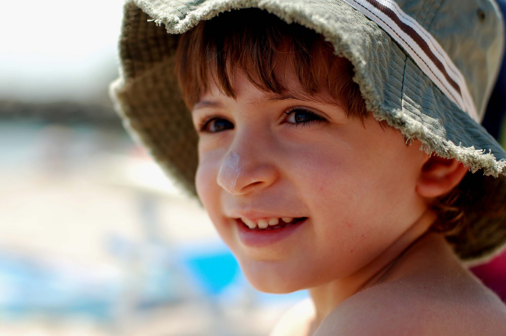 child with sunblock and hat