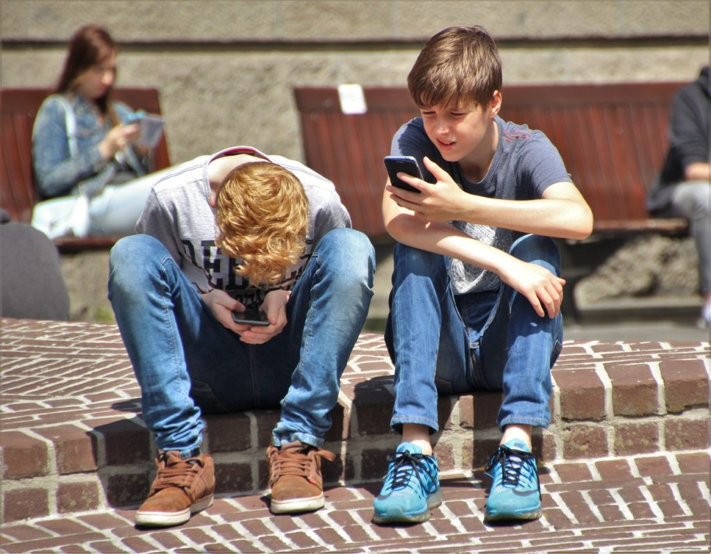 photo: pexels https://www.pexels.com/photo/2-boy-sitting-on-brown-floor-while-using-their-smartphone-near-woman-siiting-on-bench-using-smartphone-during-daytime-159395/