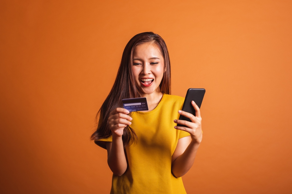 Young Asian woman using credit card and smart phone for online shopping, payment over orange background