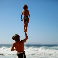 dad lifting kid beach